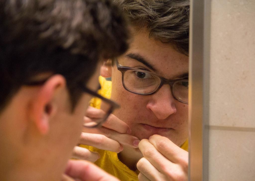 menino na puberdade espremendo espinhas em frente ao espelho